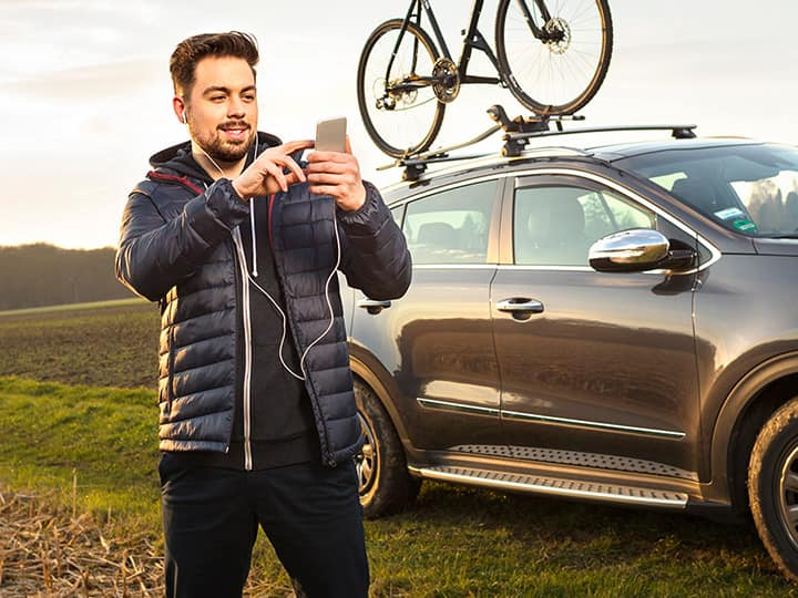 Man holding is a smartphone and searching for the best route to have a drive with his mountain bike