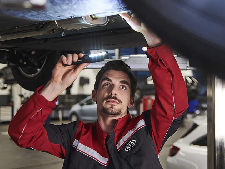 Technicien intervenant sous un véhicule pour réparer un moteur