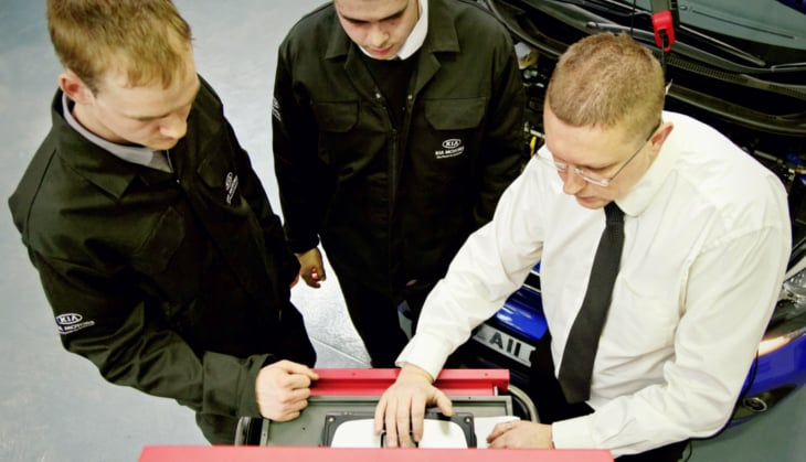 Two Kia apprentices using a laptop