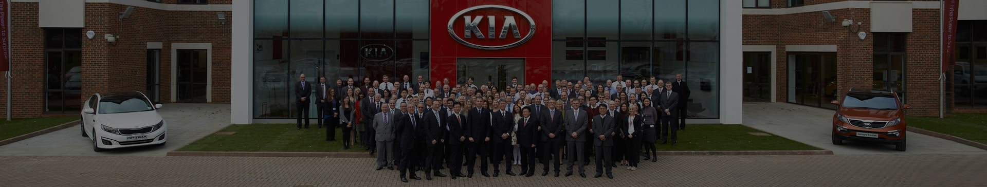 Group of Kia employees standing in front of Kia HQ