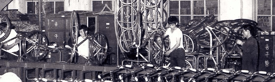 Factory workers constructing bicycles