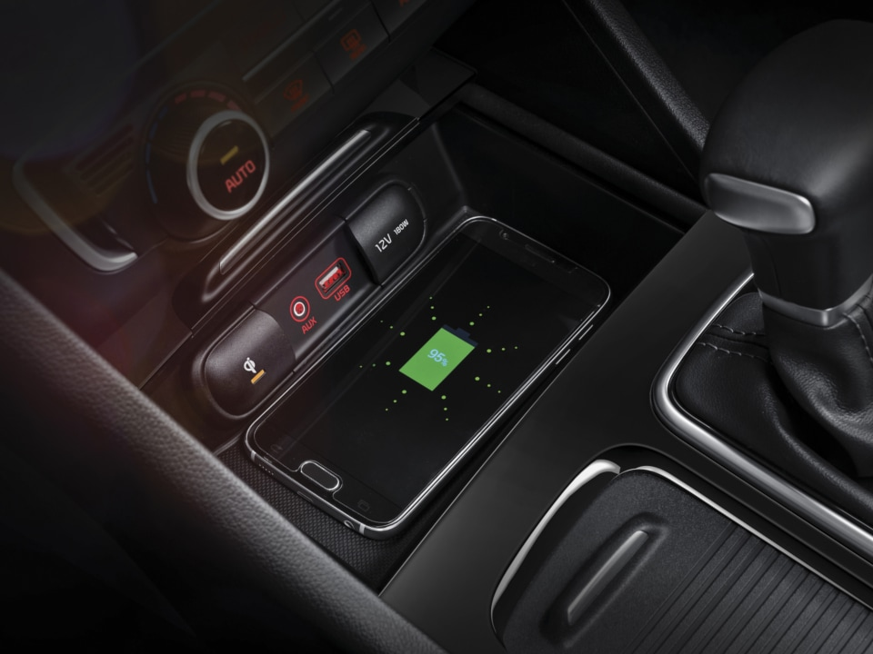 Interior shot of a mobile device charging on the wireless charging pad in front of the gear leaver in the Optima Plug-In Hybrid