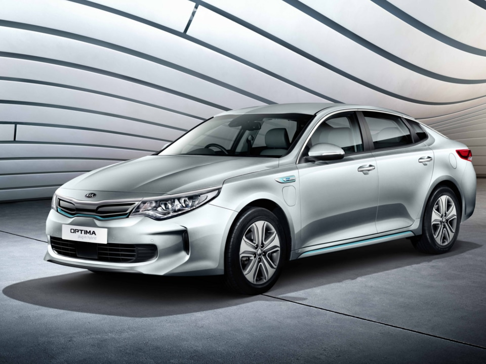 Front shot of the All-New Optima Plug-In Hybrid parked in futuristic showroom with wavey celiing
