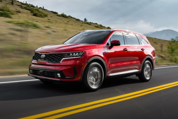 2021 Kia Sorento Turbo Hybrid in red driving on highway, 3/4 view of front driver's side