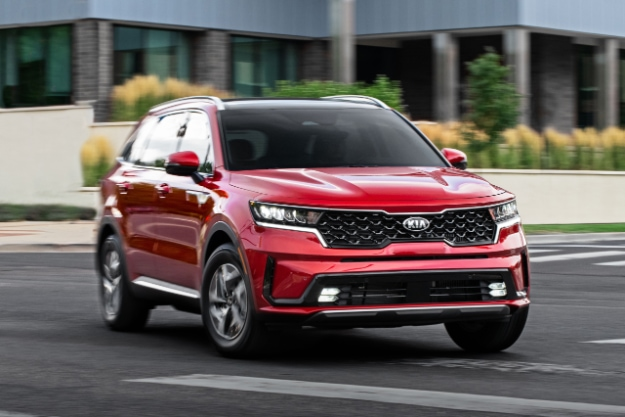2021 Kia Sorento Turbo Hybrid in red driving on highway, 3/4 view of front passenger side