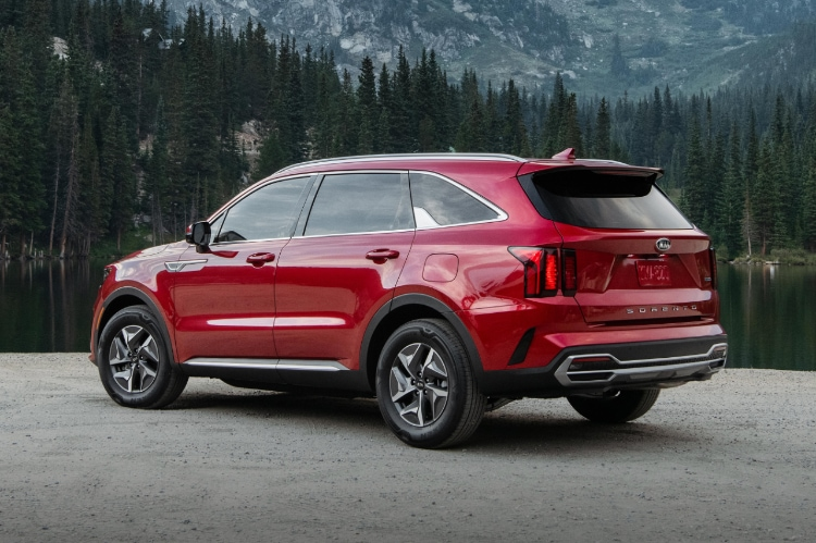 2021 Kia Sorento Turbo Hybrid in red angled to showcase the driver's side from the rear, with a scenic forest vista in the background