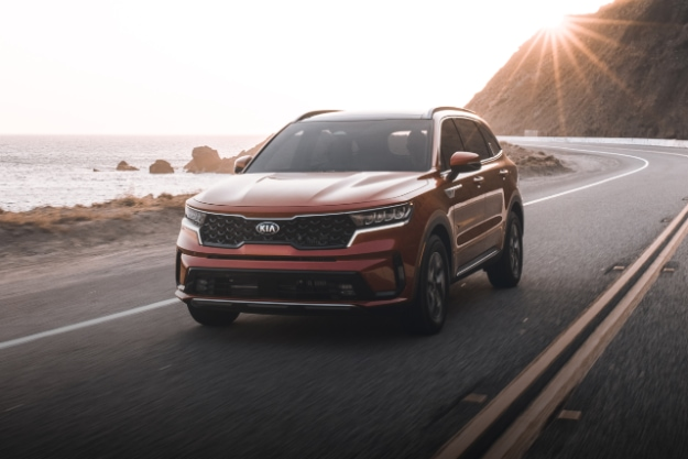 2021 Kia Sorento Turbo Hybrid in red driving on a coastal highway at sunset, front driver's side view