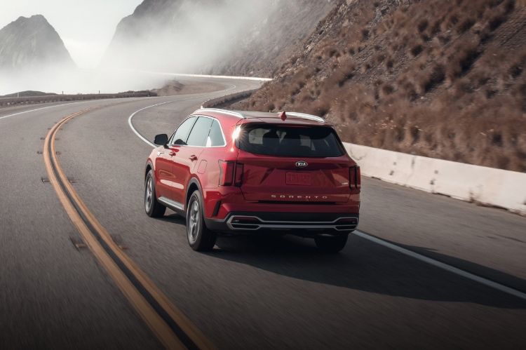 2021 Kia Sorento Turbo Hybrid in red driving on a foggy mountainside highway, rear driver's side view