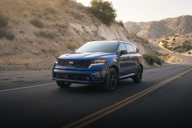 2021 Kia Sorento in blue driving down a desert highway, 3/4 view of front driver side