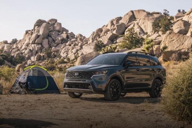 2021 Kia Sorento from 3/4 angle of front driver's side, parked at desert campsite with a tent and rugged background terrain