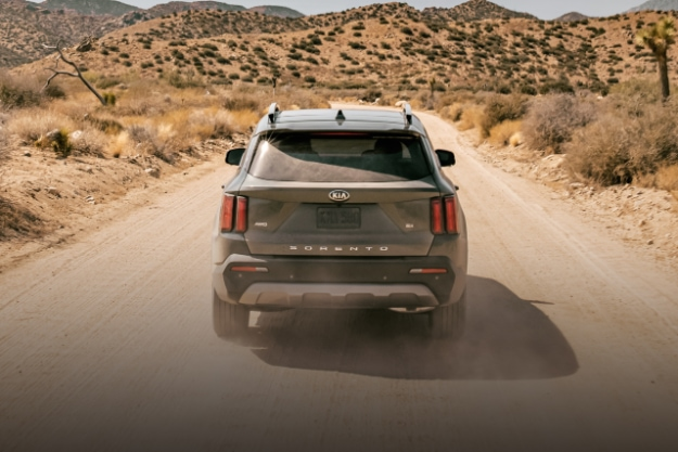 2021 Kia Sorento driving down a dusty desert trail, view from rear
