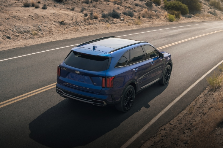 2021 Kia Sorento driving on highway, aerial 3/4 view of rear passenger side
